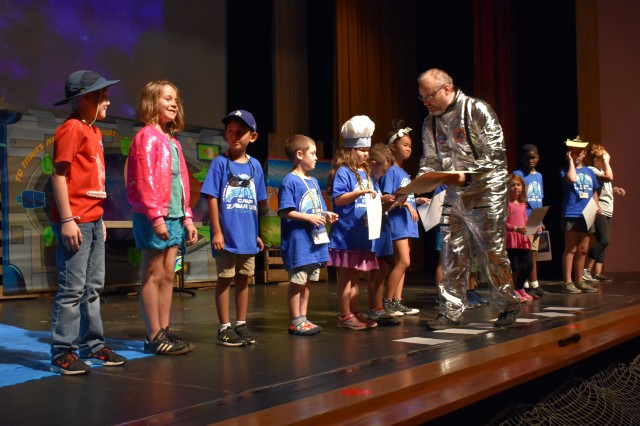 Scott Yeager, right, director of religious education, U.S. Army Garrison Japan, hands out awards to children during Vacation Bible School at Camp Zama, Japan, July 31.