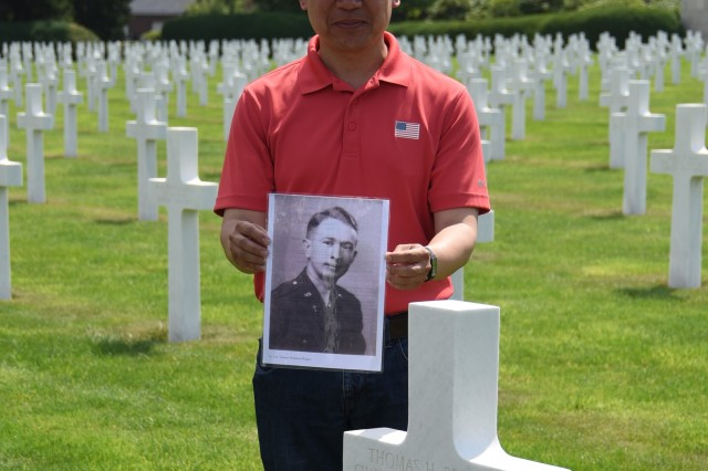 U.S. Army Garrison Benelux's Religious Support Office Soldiers and their families visited Henri-Chapelle American Cemetery near Welkenraedt, Belgium, July 25, 2019, for unit training. Chaplain (Capt.) Paul Camiring holds a photo of Army Lt. Col. Thomas Hampton Reagan as the group visited Reagan's grave stone in the cemetery.