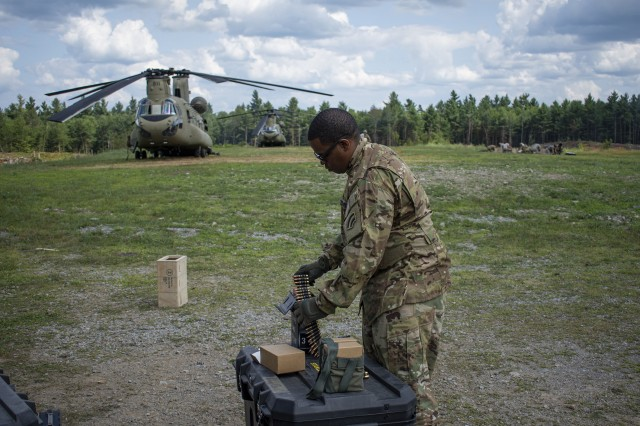New York National Guard Sergeant Gregory Moore, a member of 3rd Battalion 142nd Aviation Regiment, prepares ammo for the annual aerial gunnery at Fort Drum on Wednesday, July 24, 2019. In the background are CH-47s assigned to Bravo Company, 3rd Battalion, 126th Aviation, which also took part in the gunnery training.