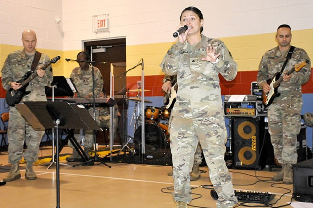 Sgt. Amanda Tetreault and the 3rd ID rock band performs songs to help open the DoDEA back-to-school rally for teachers and staff, July 29 on Fort Stewart at Kessler Elementary School on Fort Stewart. (Photo by Pat Young)