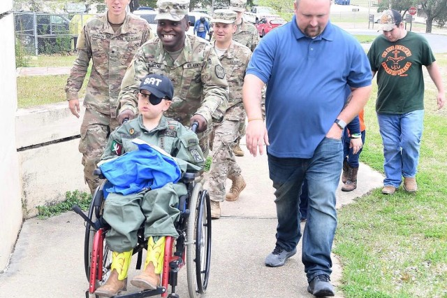 Cpl. Devon Douglas with a terminally ill child who was made a Soldier for the day at Fort Polk, a community service event Douglas helped plan. Courtesy photo