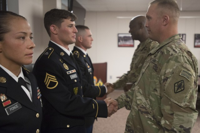 "Staff Sgt. Dakota Bowen, shakes the hand of Post Command Sgt. Maj. Jerimiah Gan, after being named Fort Jackson's best non-commissioned officer.  Bowen competed and won at the next higher level, the TRADOC Best Warrior Competition at Fort Rucker, Ala. He will compete again later this year for the highest honor for the Department of the Army Best Warrior Competition. In the background, Brig. Gen. Milford H. ""Beags"" Beagle Jr., Fort Jackson commander, congratulates another Soldier."