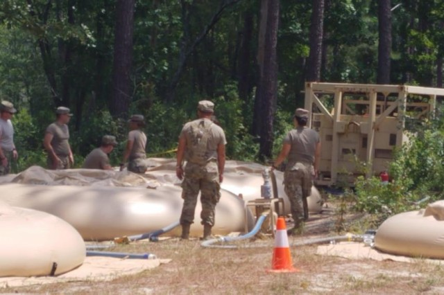 Members of the 973rd Quartermaster Company from Ceiba, Puerto Rico, fill four water cells with clean, purified water they created using a 1500 Tactical Water Purification System, or TWPS.