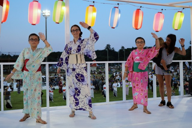 CAMP ZAMA, Japan - Chelsey DeCastro, Hemet, California native, with twin daughters, Lilly and Layla, along with Rayanna Sherman, Birmingham, Alabama native, all family members with 38th Air Defense Artillery Brigade, perform Bon Dance during the 60th Annual Camp Zama Bon Odori Festival, Aug. 3, 2019. For the first time ever, Soldiers and family members with 38th ADA Brigade participated in the festival to learn more about Japanese culture and share experiences with their host-nation neighbors.