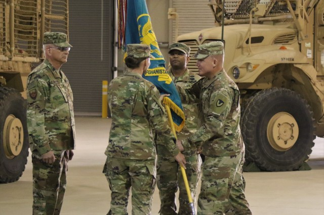Col. Charles A. Fisher, commander of the 401st Army Field Support Brigade,  passes the unit colors to Lt. Col. Virginia Knorr, the incoming commander, during the unit's change of command ceremony at Bagram Air Field, Afghanistan, July 4, 2019. The passing of the unit colors is a tradition practiced when an outgoing commander has finished their time in command and a new commander takes charge of the unit. (U.S. Army photo by Sgt. Walter Carroll)