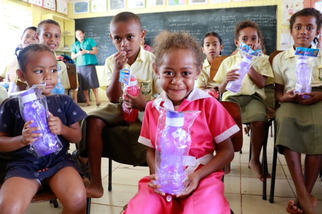 Children from the Ulubau District School pose for a group photo with water bottles donated during a civic and community relations event with the 351st Civil Affairs Command in Labasa, Fiji, July 31, 2019.Bilateral exercises, such as Exercise Cartwheel, strengthen our nations' capabilities to respond to crisis situations. The U.S. Army is committed to maintaining a long lasting relationship with its Fijian partners in the Pacific. (U.S. Army Photo by 1st Lt. Mark Sagvold)