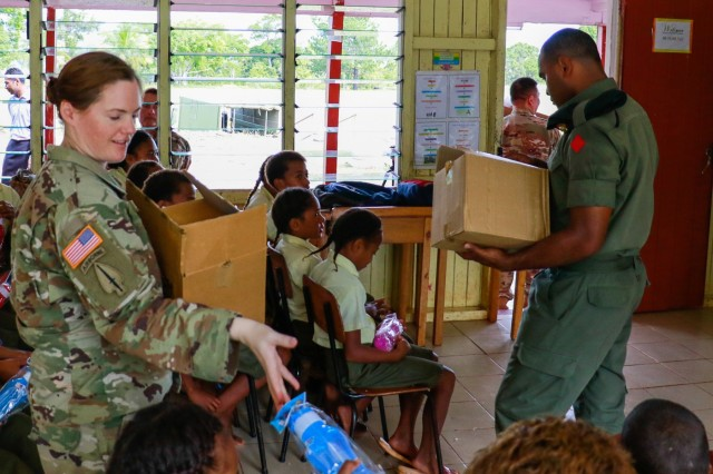 U.S. Army Maj. Kellie Landauer, who serves with U.S. Army Pacific, as an exercise planner, and a Fijian Soldier from the 1st Battalion, 3rd Fiji Infantry Regiment, hand out donated water bottles in an effort to increase the amount of water children drink during a civil and community outreach activity at Ululbau District School in Labasa, Fiji, July 31, 2019. Bilateral exercises, such as Exercise Cartwheel, strengthen our nations' capabilities to respond to crisis situations. The U.S. Army is committed to maintaining a long lasting relationship with its Fijian partners in the Pacific.(U.S. Army Photo by 1st Lt. Mark Sagvold)