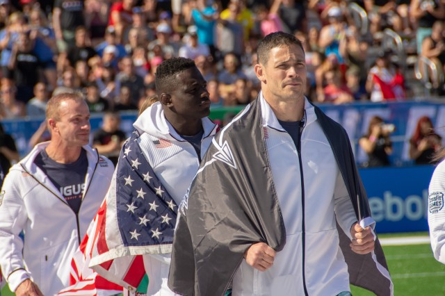 Lt. Col. Anthony Kurz and Capt. Chandler Smith, representing the U.S. Army Warrior Fitness Team, march onto the field during the 2019 CrossFit Games opening ceremony in Madison, Wis., Aug. 1, 2019. Kurz proudly displayed his U.S. Army Special Forces flag as a nod to the Special Forces community.