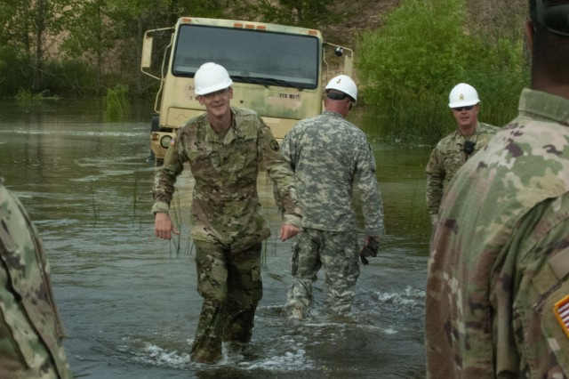 U.S. Army Reserve Soldiers with the 445th Transportation Company from Waterloo, Iowa, walk through deep water during an equipment recovery exercise at Fort McCoy, Wis., July 20, 2019.