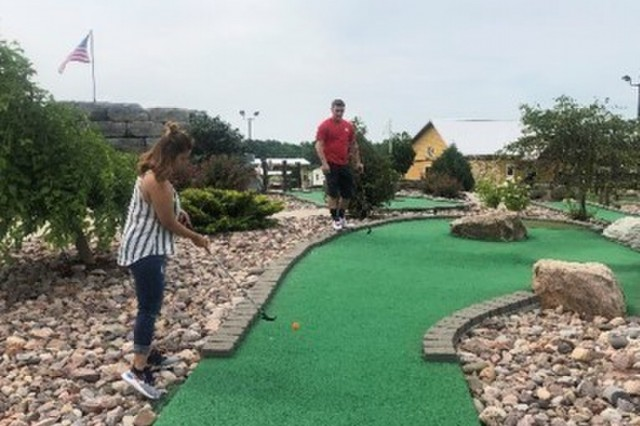 U.S. Army Pfc. Zachary Houston (in red) waits his turn to put while watching Sgt. Jessica Fiel during a miniature golf outing with the Warrior Transition Battalion, Fort Drum, New York. July 11, 2019 Clayton New York. (Photo courtesy Fort Drum WTB)