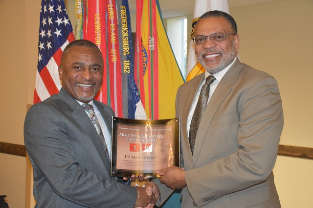Norvel Turner Jr., right, safety director for Army Central Command, accepts a fiscal year 2016 safety award on behalf of a unit in the command during a ceremony in April 2017. Turner, a former Army Ranger, helped save a man's life June 27, 2019, while on a commercial jet awaiting to depart from Charlotte.