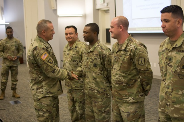 CSM Rodger W. Mansker, AMC, presents coins of excellence at the 2019 HQDA G-4 Sustainment Senior Enlisted Leader Development Symposium.