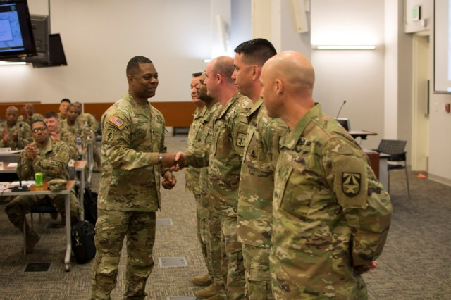 SGM Edward A. Bell, HQDA, G-4, presents coins of excellence at the 2019 HQDA G-4 Sustainment Senior Enlisted Leader Development Symposium.