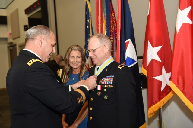 Maj. Gen. Allan Elliott, receives honors at his May 28 retirement from Army Materiel Command Commanding General Gen. Gus Perna, who officiated at the ceremony. Elliott retired as AMC's chief of staff during a retirement ceremony at AMC Headquarters. With them is Elliott's wife, Sharon. (U.S. Army Photo by Doug Brewster)