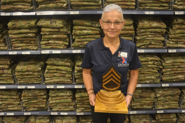 """Rosa Isern, Fort Gordon Military Clothing and Sales store manager, poses with a gift she received from several beloved platoon sergeants upon her return from deployment, deeming her an """"honorary staff sergeant."""""""