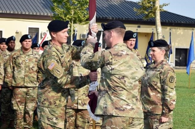 Lt. Col. Leif O. Ibsen, incoming commander of Public Health Activity - Italy, receives the Battalion Colors from Col. Brian C. Spangler, commander of Public Health Command Europe, during the change of command ceremony at Caserma C. Ederle in Vicenza, Italy, July 30, 2019.