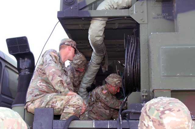 Staff Sgt. Tyler Wegman (wearing patrol cap), a 14E AIT instructor, watches as students hookup power cables to the engagement control station (ECS) July 31, 2019, at the Patriot General Instruction Facility at Fort Sill, Okla. In addition to the ECS, 14E Soldiers operate/maintain a radar, electronic power plant, and antennae mast group.