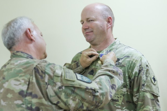 1st Sgt. Darren Rone , 184th Sustainment Command, was pinned with an Army Achievement Medal by Lt. Col. Stephen McCarthy while for serving as the noncommissioned officer in charge of  the torch party during the units mobilization activities at Fort Hood, Texas, during a town hall meeting at Camp Arifjan, Kuwait, May 25, 2019. (U.S. Army National Guard photo by Staff Sgt. Veronica McNabb)