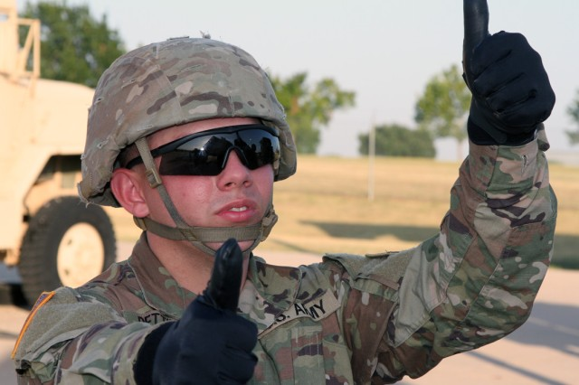 Patriot Fire Control Enhanced Operator/Maintainer AIT student Pvt. Jedidiah Pettinari, 21, from Colorado Springs, Colo., gives hand signals to operators lowering a phased array radar July 31, 2019, at Fort Sill, Okla., during an FTX.