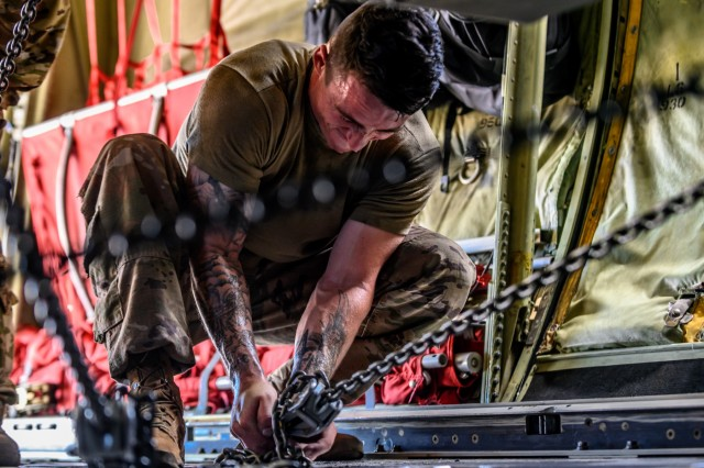 Staff Sgt. Justin Hoffman, a M142 High Mobility Artillery Rocket System (HIMARS) section chief assigned to 1st Battalion, 14th Field Artillery Regiment, 75th Field Artillery Brigade, Fort Sill, OK, uses chains to secure a HIMARS on an Airforce C-130J Super Hercules at Henry Post Army Airfield in preparation for a cold-load air/land raid exercise to Dyess Airforce Base, Texas, July 24, 2019. The cold-load air/land raid exercise provides both Soldiers and Airmen with hands-on experience loading and securing an M142 High Mobility Artillery Rocket System onto an Aircraft, enhancing both organizations overall lethal capabilities.  (U.S. Army photo by Sgt. Dustin D. Biven / 75th Field Artillery Brigade)