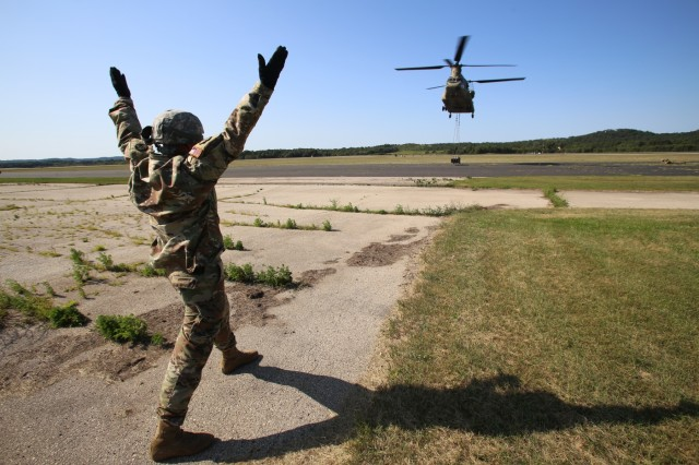 Master Sgt. Jack Kenyon, course manager for the 89B Ammunition Supply Course with the 13th Battalion, 100th Regiment at Fort McCoy, Wis., provides lift guidance from a distance Aug. 1, 2019, to a Chinook helicopter crew during sling load training for the course at Sparta-Fort McCoy Airport. The Chinook and crew are from the 7th Battalion, 158th Aviation Regiment of New Century, Kansas. The Ammunition Supply Course is a four-week course that provides training for Soldiers who are reclassifying to the 89B military occupational specialty. The sling-load training is one of the last major training events during the course. A sling load is used to transport munitions to remote locations or to expedite shipments in hostile locations. (U.S. Army Photo by Scott T. Sturkol, Public Affairs Office, Fort McCoy, Wis.)