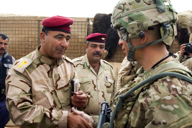 Command Sgt. Maj. Michael Grinston, right, senior enlisted leader for 1st Infantry Division, presents a coin to the officer in charge of providing chow for Iraqi army soldiers training at Al Asad Air Base, Iraq, Jan. 15, 2015. Grinston was sworn in as the 16th sergeant major of the Army on Aug. 9, 2019. As the top enlisted leader in the Army, one of his priorities will be for Soldiers to master the fundamentals -- the basic individual combat tasks and skills they should all know.