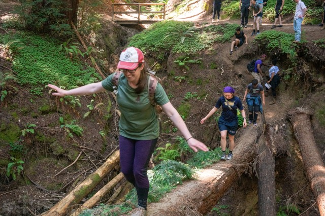 Spc. Melody Sobey, an Army linguist student in the 229th Military Intelligence Battalion, Defense Language Institute Foreign Language Center, crosses a fallen redwood tree during a 'Spiritual Fitness Hike' at Henry Cowell Redwoods State Park in Fulton, Calif., July 27, 2019.