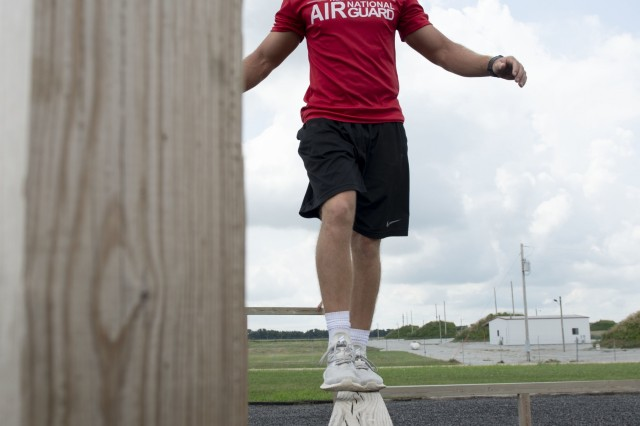 Conner Stutheit, a student flight trainee with the 155th Air Refueling Wing, crosses a balance beam as part of the obstacle course Aug. 3, 2019, at the Army National Guard's Greenlief Training Site near Hastings, Nebraska. This obstacle was one of four selected obstacles that the Nebraska Air National Guard's student flight and the Nebraska Army National Guard's Recruit Sustainment Program had to complete during the Student Flight RSP Challenge on Saturday. (U.S. Air Force photo taken by Senior Airman Jamie Titus)