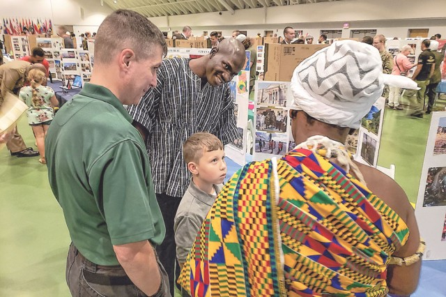 Capt. Alice Anoi, right, and Maj. Carlin Tawiah-Martins, center, both from the Republic of Ghana, showcase their display for Lt. Col. Matthew Prohm and his son, Frederick, 8, during the Know Your World event Friday at Nutter Field House.