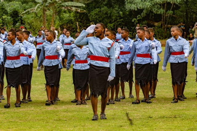 A cadet platoon leader salutes and commands a group of student cadets as they march on the parade field at the Napuka Secondary School for graduation in Napuka Village, Fiji, Aug. 7, 2019. U.S. and Fijian Soldiers attended the event and did a tactics display for the event to showcase the jungle training done during Exercise Cartwheel 2019. Exercise Cartwheel is a U.S. Army Pacific sponsored military training, and community engagement event under the Pacific Pathways program. The exercise demonstrates the U.S. Army's enduring commitments to Fiji, and promotes cooperation and interoperability with our partners in a free and open Indo-Pacific. (U.S. Army photo by Sgt 1st Class Whitney Houston)