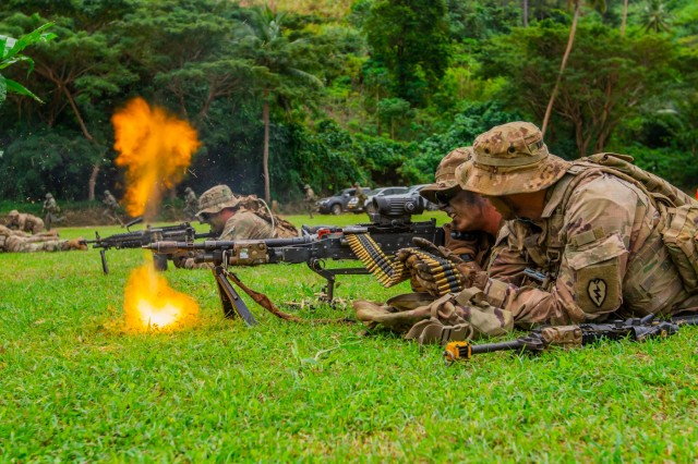 Sgt. David Knack (right), feeds blank ammunition into a 240B machine gun that Spc. Zachary Parady fires during a military tactics demonstration at a Fijian cadet graduation in Napuka Village, Fiji, Aug. 7, 2019. Both Soldiers serve with the 1st Battalion, 27th Infantry Regiment, 2nd Brigade, Inf. Brig. Combat Team, 25th Inf. Division, and have been training alongside the 3rd Btn. Fiji Inf. Regt., during Pacific Pathway's Exercise Cartwheel 2019. The display was to showcase a jungle situational exercise that the group had been working on during the exercise. Bilateral training develops the RFMF capabilities and increased the strength and security of both military forces for a free and open Indo-Pacific region.(U.S. Army Photo by Sgt. 1st Class Whitney Houston)