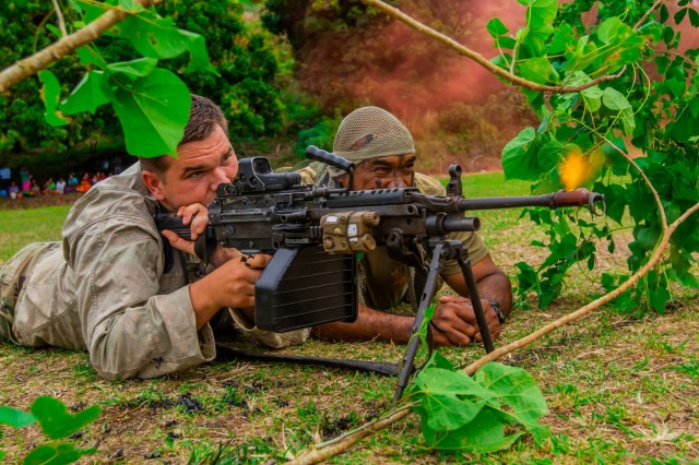 U.S. Spc. Christian Latham (left), who serves with 1st Battalion, 27th Infantry Regiment, 2nd Brigade, Inf. Brig. Combat Team, shoots a squad automatic weapon as an opposition force with his Fijian partner Fijian Sgt. Iowane Seru, who serves with 3rd Btn. Fiji Inf. Regt., during a cadet graduation in Napuka Village, Fiji, Aug. 7, 2019. The display for the event was to showcase the joint jungle training exercise done during Pacific Pathway's Exercise Cartwheel 2019. Bilateral training develops the RFMF capabilities and increased the strength and security of both military forces for a free and open Indo-Pacific region.