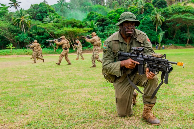 Fijian Corporal Tora, who serves with the 3rd Battalion, Fiji Infantry Regiment, kneels in position while U.S. Soldiers serving the 1st Btn., 27th Inf. Regt., 2nd Brigade, Inf. Brig. Combat Team, 25th Inf. Division, move in a wedge formation behind him during a Fijian cadet graduation in Napuka Village, Fiji, Aug. 7, 2019. The display for the event was to showcase the joint jungle training exercise done during Exercise Cartwheel 2019. Bilateral training develops the RFMF capabilities and increased the strength and security of both military forces for a free and open Indo-Pacific region.