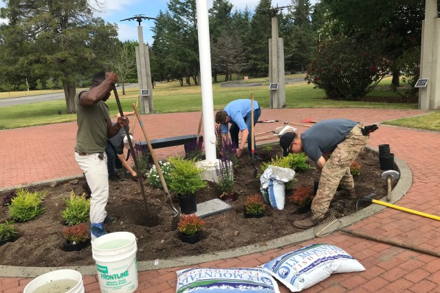 Some of the volunteers tend to the flower and plant bed at the McChord Field Memorial Grove on Joint Base Lewis-McChord recently.