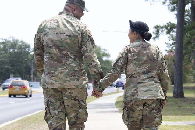 Staff Sgt. Joshua Mitchell, left, walks with his wife Spc. Eunjee Mitchell during the Fort Jackson Family Day on July 31. Spc. Mitchell recently graduated Basic Combat Training at the post. Her husband, an Army recruiter, enlisted his wife as she spent two years listening to him explain the benefits of military service to potential future Soldiers.