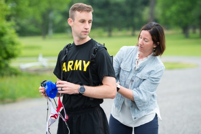 Megan Amadeo, Army Wellness Center project officer, Army Public Health Center,  assists Headquarters and Headquarters Company commander, Army Public Health Center, with putting on the new K5 metabolic testing unit May 9, 2019, as part of his training to compete in the Army Ten Miler in October 2019. The K5 portable VO2 unit, which is available at certain Army Wellness Center locations, allows Soldiers and athletes to measure how well their muscles use oxygen, and can be used to optimize performance and train for events. (U.S. Army photo by Graham Snodgrass).