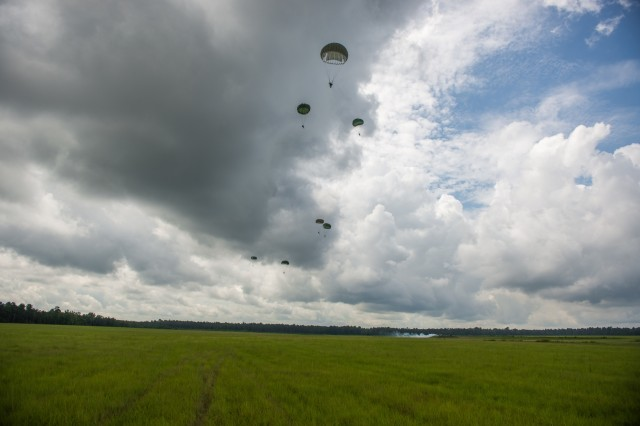 FORT BENNING, Ga. -- In this U.S. Army file photo from 2018, parachutists in World War II period uniform drop from a restored Douglas C-33 aircraft over Fryar Drop Zone as part of National Airborne Day. The Maneuver Center of Excellence and Fort Benning is scheduled to host the 2019 National Airborne Day event beginning 9 a.m. Aug. 16 at Fryar Drop Zone with freefall parachute jump demonstrations by two separate jump teams, followed by a graduation ceremony of the nation's newest paratroopers. (U.S. Army file photo by Patrick Albright, Maneuver Center of Excellence, Fort Benning Public Affairs)