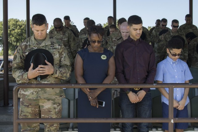 Command Sgt. Maj. Kim Mendez and his family participate in an invocation before the 3rd Cavalry Regiment's change of responsibility ceremony at Cameron Field Aug. 12. (U.S. Army photo by Staff Sgt. Justin Geiger)