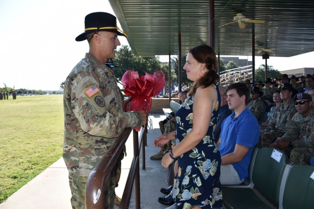Sgt. Maj. Adam Nash presents his wife, Mrs. Erin Nash, a traditional bouquet of red roses during the 3rd Cavalry Regiment's change of responsibility ceremony at Cameron Field Aug. 12. (U.S. Army photo by Capt. Jo Nederhoed)
