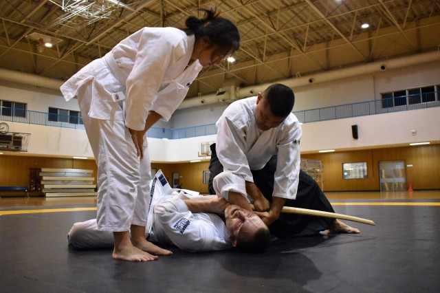 Dwayne Suwa, right, demonstrates an aikido sword technique with Joe Millen, center, an engineer with the U.S. Army Corps of Engineers, Japan Engineer District, during an aikido class at the Yano Fitness Center, Camp Zama, Japan, Aug. 8. Maryn Nakasone, left, an animal health assistant at the Camp Zama Veterinary Treatment Facility, looks on.