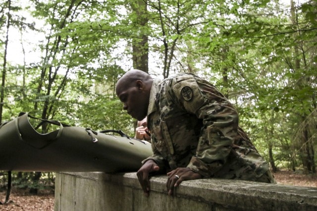 U.S. Army Sgt. 1st Class Christopher Moore, noncommissioned officer in charge, Troop Command, LRMC,negotiates a wall obstacle during tate a simulated patient as part of the Litter Obstacle Course during LRMC's 2019 Best Medic competition, Aug. 6.