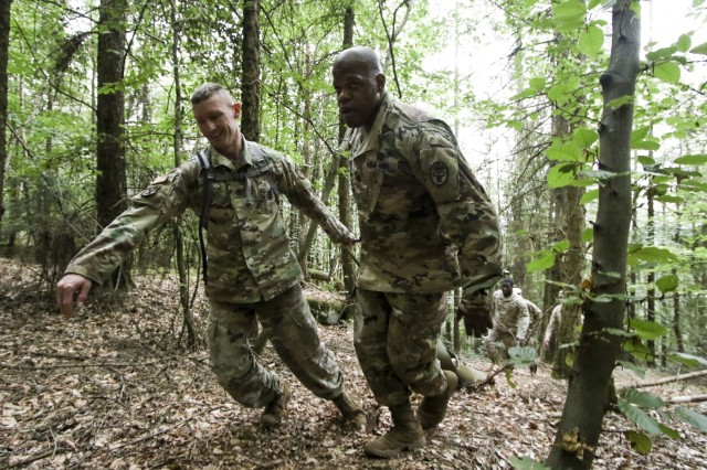 U.S. Army Staff Sgt. Joseph Coffey (left), operations noncommissioned officer, Troop Command, Landstuhl Regional Medical Center, and U.S. Army Sgt. 1st Class Christopher Moore, noncommissioned officer in charge, Troop Command, LRMC, negotiate an obstacle as part of the Litter Obstacle Course during LRMC's 2019 Best Medic competition, Aug. 6.