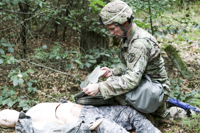 U.S. Army Staff Sgt. Joseph Coffey, operations noncommissioned officer, Troop Command, Landstuhl Regional Medical Center, performs first aid on a simulated casualty as part of the Combat Testing Lane during LRMC's 2019 Best Medic competition, Aug. 6.