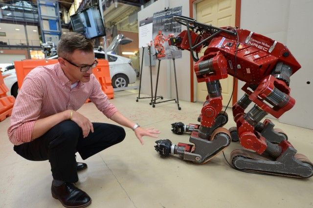 Josh Cauvel, program manager for the Artificial Intelligence Hub at Carnegie Mellon University, points out characteristics of CHIMP, a humanoid robot at the National Robotics Engineering Center that won third place in a contest sponsored by DARPA in 2015. Part of Cauvel's job is to help the Army's AI Task Force collaborate with researchers at CMU and other universities.