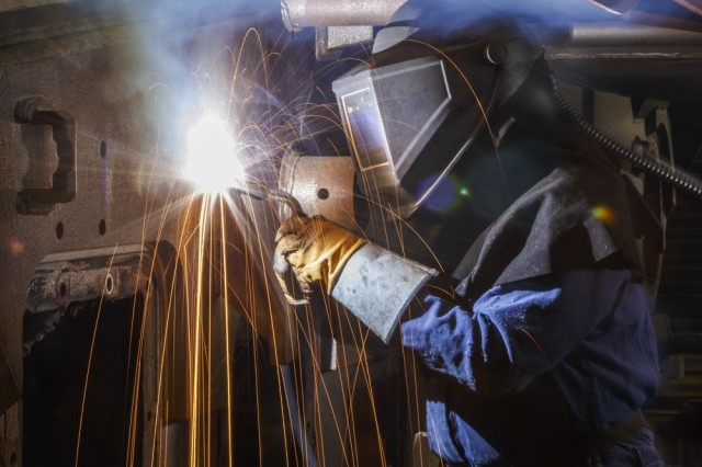Roy Bearden performs flux cored arc welding on a M1 tank. Flux cored arc welding is used to remove impurities when the metal being welded isn't clean. At Anniston Army Depot, it may be seen on rusty hulls, among other applications.