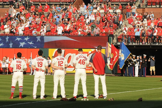 St. Louis Cardinals players and fans stand with their hands over their hearts during the playing of the national anthem by the 399th Army Band as the Fort Leonard Wood Joint Services Color Guard presents the colors.