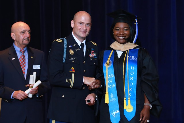 FORT BENNING, Ga. -- Lakeitha Smiley-Hooks, a budget analyst with the Maneuver Center of Excellence and Fort Benning, shakes hands with U.S. Army Garrison Fort Benning Commander Col. Matthew Scalia. Smiley-Hooks graduated with honors from American Military University, earning a Master of Business Administration with a concentration in finance. Fort Benning graduates who finished their college degrees from different schools across the country during the 2018-2019 school year received their degrees during a ceremony here Aug. 9, 2019. (U.S. Army photo by Markeith Horace, Maneuver Center of Excellence, Fort Benning Public Affairs)