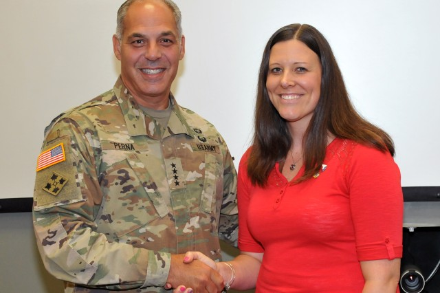 Gen. Gus Perna, Commander, U.S. Army Materiel Command, presented Tara Jackson, Planning Directorate, an AMC coin for developing a workload plan and accountability measures that incorporated increased depot efficiencies across the munitions enterprise and improved readiness, August 13.