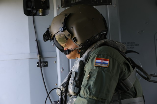Flight engineer, Croatian Air Force Master Sgt. Marinko Gudeljevic observes the area of operation in Kosovo during a flight pattern with Kosovo Force's Task Force Aviation, beginning at Camp Bondsteel, Aug. 6, 2019. The role of the flight engineer is to advise the pilot of any problems, make record of any flight issues and observe the overall performance of the helicopter. (U.S. Army photo by Spc. Grant Ligon, 40th Public Affairs Detachment)