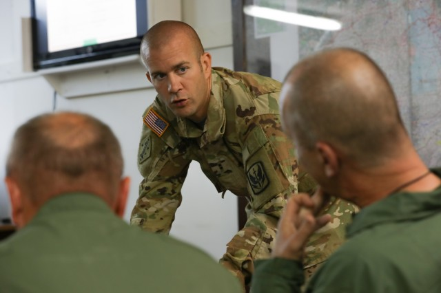 Chief Warrant Officer 2 Stephen Gayton, an instructor pilot with Task Force Aviation's 1st Battalion, 171st Aviation Regiment, explains details of the day's flight brief with the Croatian Air Force's aviation team on Camp Bondsteel, Kosovo, Aug. 6, 2019. This training mission improves interoperability between NATO partners and prepares TF Aviation for future Kosovo Force operations. (U.S. Army photo by Spc. Grant Ligon, 40th Public Affairs Detachment)